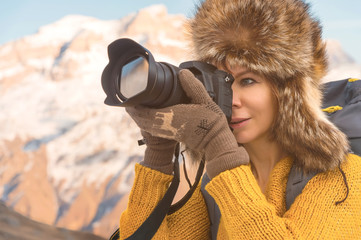 Portrait of a sweet tourist girl in a big fur hat takes pictures on her digital camera in the mountains.