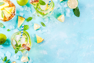 Tropical drink,  Pineapple mojito or lemonade with fresh lime and mint  light blue background, copy space top view