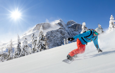 Young man snowboarder running downhill in Alps