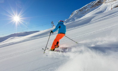 Young man skiing downhill in Alps