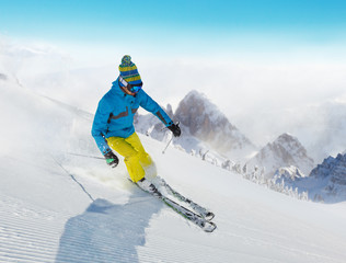 Fototapete - Young man skiing downhill in Alps