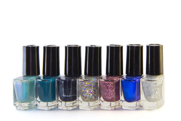 Glass bottles of nail polish with fashionable different shades of the year (blue, green, purple, violet) stand in a row, isolated on white background