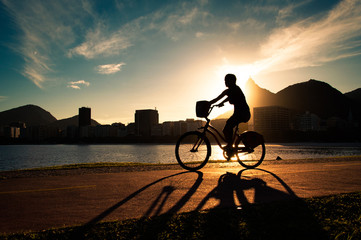 Silhouette of a Woman Cycling in Rio de Janeiro by Sunset with Corcovado Mountain in Background