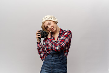 concept of retro youth, old school photography and hipster fashion. Young blond woman in a white knitted cap with a smile, posing for portrait with camera in hands. Denim overalls and plaid shirt