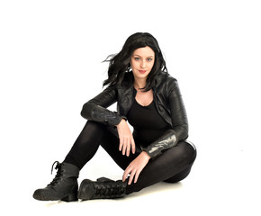full length portrait of black haired girl wearing leather outfit. sitting pose, isolated on a white studio background.