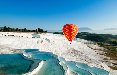 Hot air balloon flying over Travertine pools limestone terraces in Pamukkale, Denizili, Turkey Fototapete