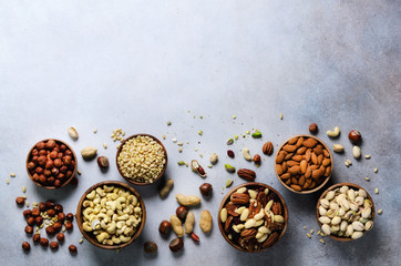 Assortment of nuts in wooden bowls. Cashew, hazelnuts, walnuts, pistachio, pecans, pine nuts, peanut, raisins. Food mix background, top view, copy space, banner.