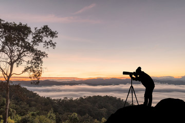 silhouette of a photographer who shoots a sunset