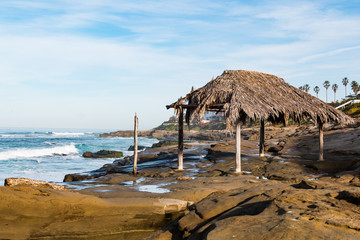 Windansea Beach with surfer shack, a historical landmark, atop rock formations.