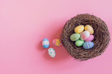 Colorful easter eggs in nest on pink pastel color background with space.