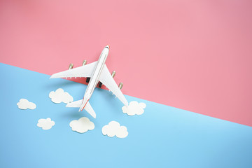 Flat lay design of travel concept with plane and cloud on blue and pink background with copy space.