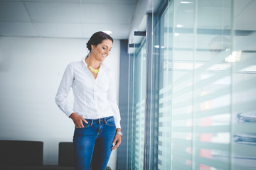 Beautiful brunette business woman standing in a boardroom
