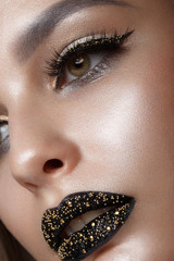 Beautiful girl with black creative art make-up. Beauty face. Photos shot in studio