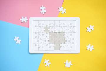 White jigsaw puzzle on blue, pink and yellow background.