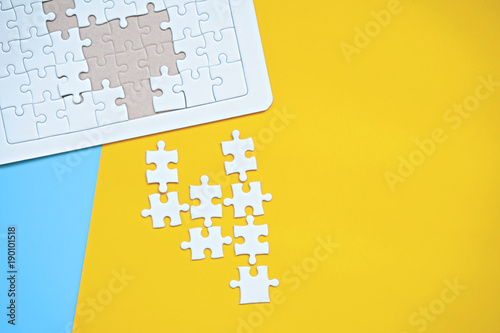 White jigsaw puzzle on blue and yellow background