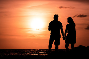 Valentine's day romantic time, The couple silhouette at twilight on the beach, together is feel happy, copy space.