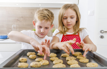 Two children having fun baking in the kitchen. A boy and a girl cooking.