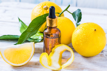Citrus bergamot fruit essential oil, aromatherapy or natural organic beauty cosmetic oil. Bottle of essential oil on white wooden background.