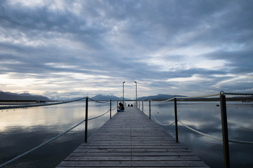 Wood bridge at sunset with calm water and clouds reflections, Puerto Natales, Chile