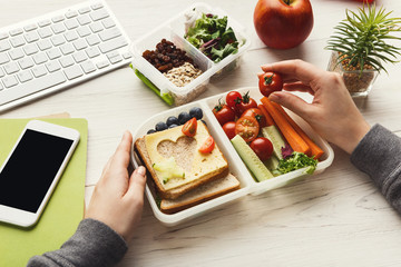 Woman eating healthy sandwich from lunch box at her working table