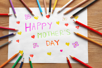 Handmade card with text HAPPY MOTHER'S DAY and pencils on wooden table