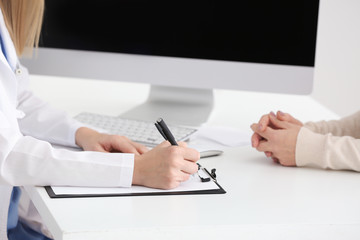 Female doctor filling up application form while consulting patient in clinic