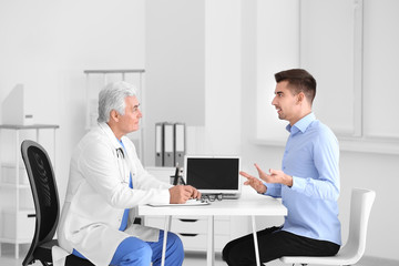 Male doctor consulting patient in clinic