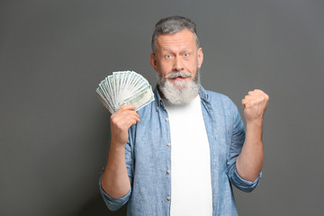 Emotional senior man with lot of dollar banknotes on grey background