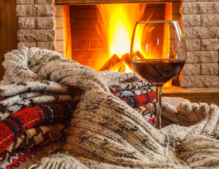 Glass of red wine; and wool; things near cozy fireplace.