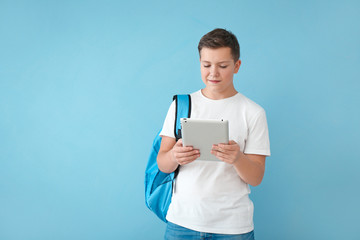 Teenage boy with backpack and tablet computer on color background