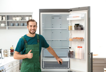 Male technician after successful repair of refrigerator indoors