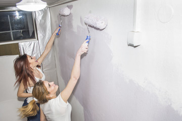 Two Smiling Attractive Young Women having fun wall painting - Spring Cleaning and Wall Painting Concept