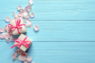 Gift boxes and petals on wooden background