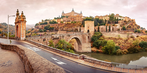Wall Mural - Panorama of Old city of Toledo with Alcantara Bridge across the river Tajo and Alcazar in the overcast evening, Castilla La Mancha, Spain