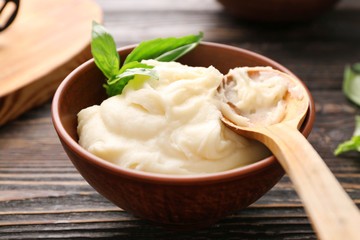 Mashed potatoes and spoon in bowl on wooden table