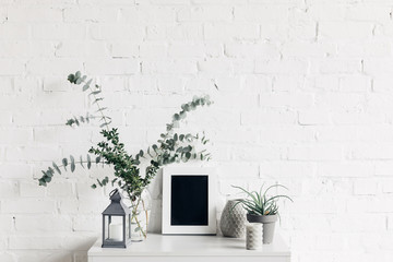 houseplants with blank small chalkboard in front of white brick wall, mockup concept