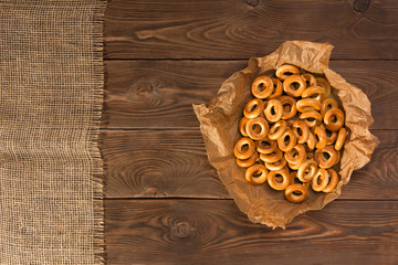 Small dry bagels on wooden table, top view.