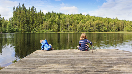 Two children using a homemade fishing rod fishing from a jetty by a lake set in an idyllic Swedish summer forest landscape.