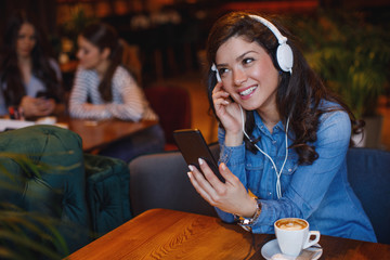 Young woman listening to music via headphones and smartphone in a cafe