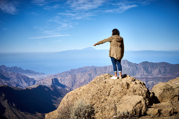 Mountain view on Canary Islands / A woman that stands on the Canary Island Gran Canaria is pointing at Volcano Teide of Tenerife