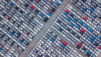 Aerial view new car lined up in the port for dealership business import and export, New car lined up parking lot outside an automobile automotive factory distribution for sale.