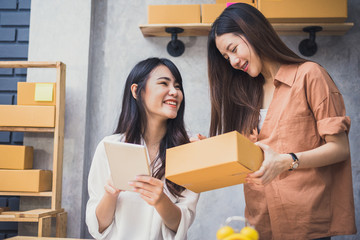 Two young Asian people startup small business entrepreneur SME distribution warehouse with parcel mail box. small  owner home office. Online marketing and product packaging and delivery service