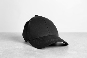Black cap on table against white background. Mockup for design