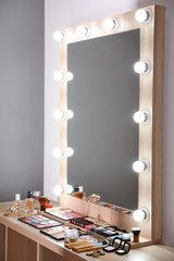 Workplace of professional makeup artist with large mirror and cosmetic