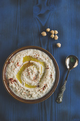 Homemade humus served in the plate on wooden background,selective focus