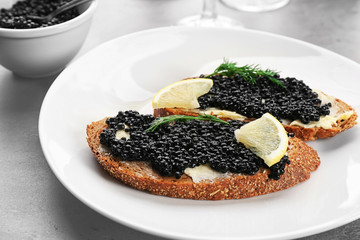 Slices of bread with black caviar and butter on plate