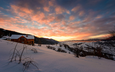 winter sunrise with red clouds in the village