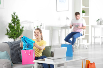 Woman with shopping bags and unhappy man at home. Money problems in relationship