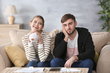Happy woman holding piggy bank and sad man with bills at home. Money problems in relationship