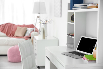 Student room interior with laptop on table